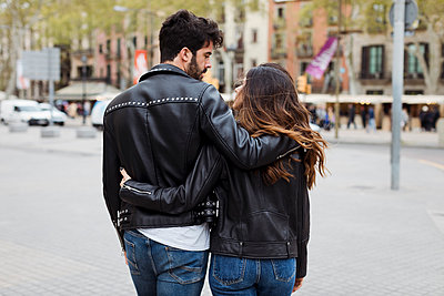 Spain, Barcelona, young couple embracing and walking in the city - p300m2023789 von Mauro Grigollo