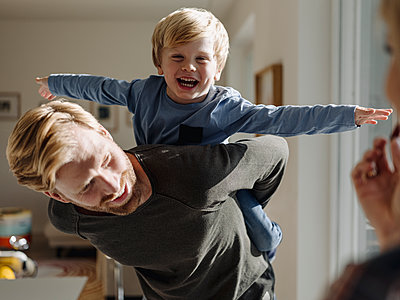Happy father carrying son piggyback at home - p300m2166588 by Kniel Synnatzschke