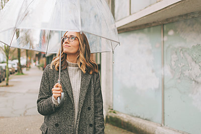 Blond woman walking in the rain with an umbrella - p300m2170012 by Crystal Sing