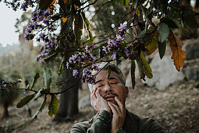 Mature man touching face while standing below blossoming tree in garden - p300m2276398 by Gala Martínez López