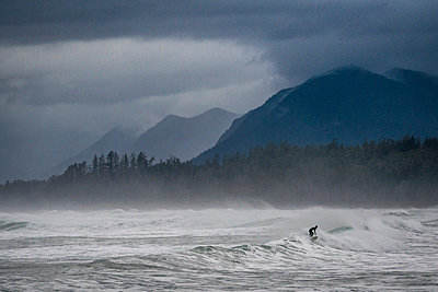Surfer on stormy day on coast - p343m1475636 by Cavan Images