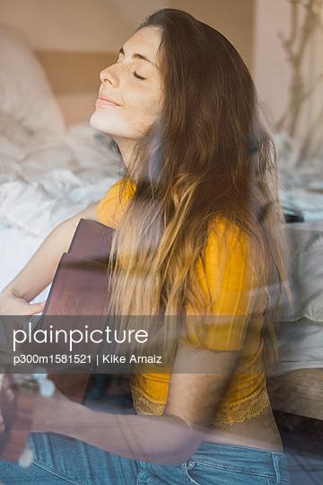 Portrait of content young woman sitting behind windowpane playing guitar - p300m1581521 von Kike Arnaiz