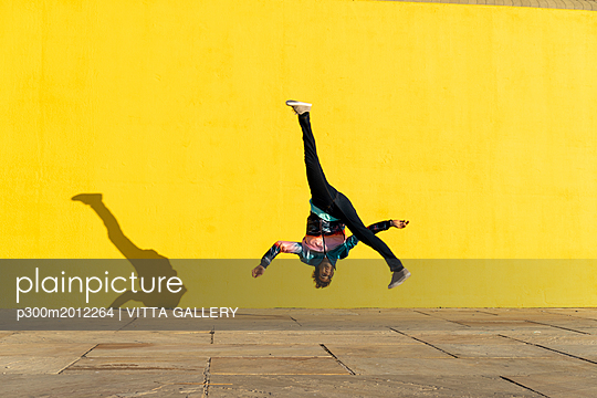 Acrobat jumping somersaults in front of yellow wall - p300m2012264 von VITTA GALLERY