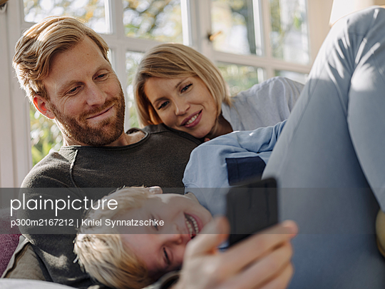 Happy family using cell phone in sunroom at home - p300m2167212 by Kniel Synnatzschke