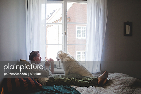 Senior man playing with dog while leaning on bed by window at home - p426m2046386 by Maskot