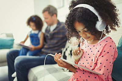 Girl with headphones using digital tablet on sofa - p1023m1448789 by Paul Bradbury