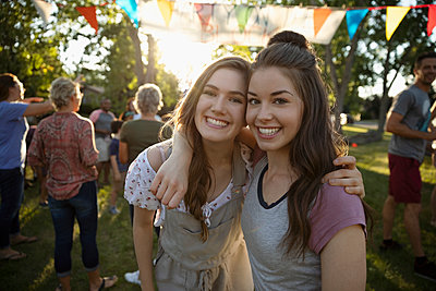 Portrait smiling teenage friends hugging at summer neighborhood block party in park - p1192m2017053 by Hero Images