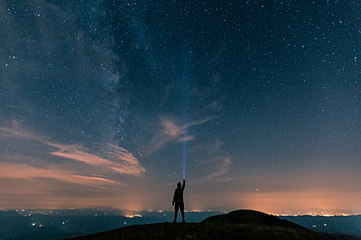 Italy, Monte Nerone, silhouette of a man with torch under night sky with stars and milky way - p300m2081530 von William Perugini