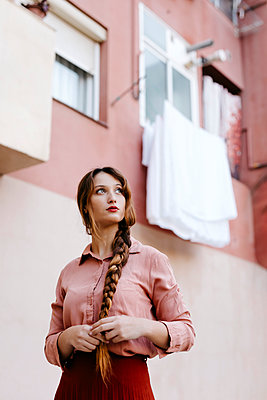 Portrait of delicate woman with very long blonde hair in vintage clothes and pink urban wall background - p300m2199529 von Tania Cervián
