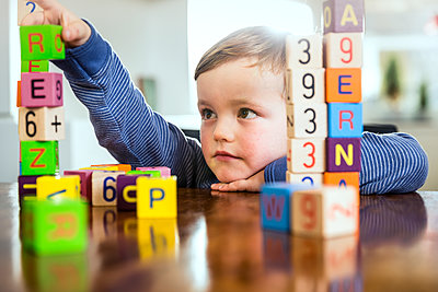Cute boy playing with toy blocks on table at home - p300m2287546 by Stefanie Aumiller
