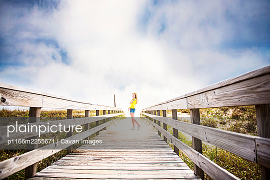 Redhead Girl on boardwalk to ocean with blue sky and clouds. - p1166m2255671 by Cavan Images