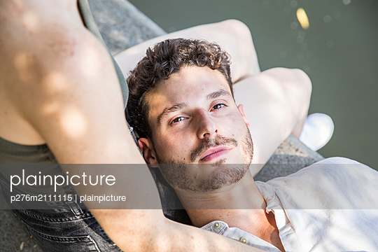 Young man lies in the lap of his girlfriend and looks into the camera - p276m2111115 by plainpicture