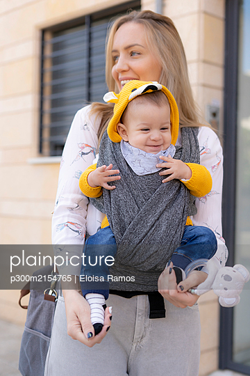 Happy mother carrying baby boy in a sling outdoors - p300m2154765 von Eloisa Ramos