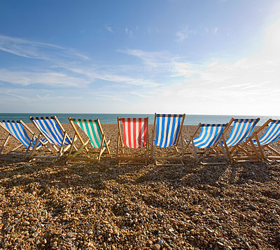 Row of striped beach chairs on a pebble beach by the ocean. - p1100m1570933 by Mint Images