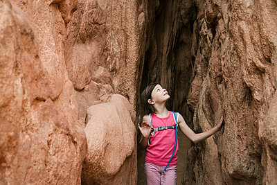 Girl looking up while standing amidst rock formations - p1166m1545458 by Cavan Social