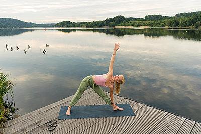 Young woman doing gymnastics on a jetty at a lake - p300m2140064 by Joseffson
