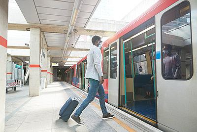 Male entrepreneur business travel boarding metro train at station during pandemic - p300m2241550 von Pete Muller