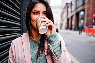 Young woman looking away while drinking coffee by shutter in city - p300m2273662 by Angel Santana Garcia
