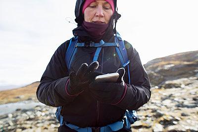 Woman using smart phone while hiking - p352m2118803 by Carina Gran