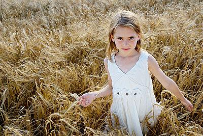 Young girl walking in corn field - p4292222f by Adie Bush