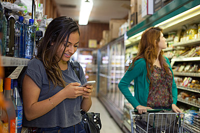 Female shopper texting on smartphone in health food store - p924m1012543f by Raphye Alexius