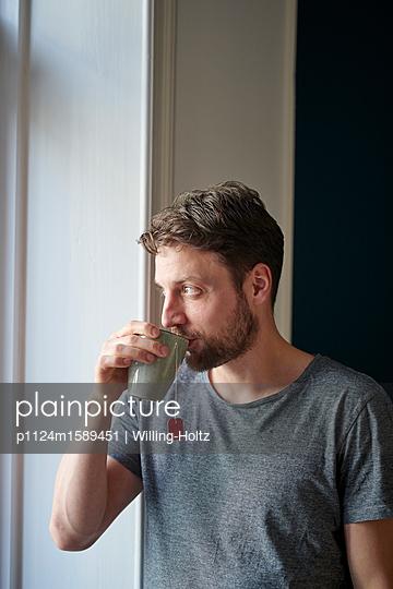 Junger Mann trinkt einen Becher Tee - p1124m1589451 von Willing-Holtz