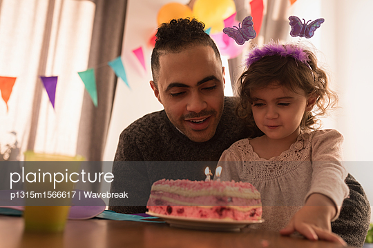 Father and daughter celebrating birthday in living room at home - p1315m1566617 by Wavebreak