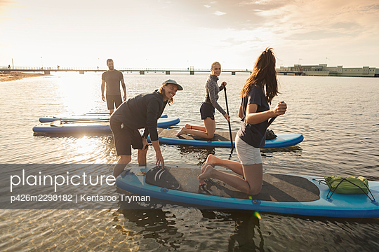 Male instructor teaching woman to paddleboard in sea - p426m2298182 by Kentaroo Tryman