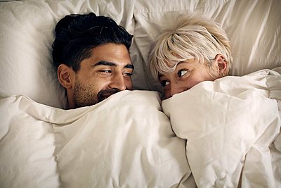 Overhead view of happy couple looking at each other in bed - p1166m1096261f by Cavan Images