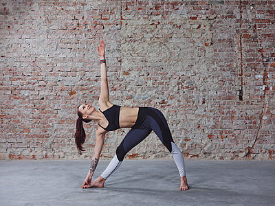 Young female in yoga pose by the brick wall - p1166m2095645 by Cavan Images