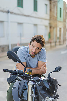 Portrait of young man sitting on motorbike - p300m1567684 by VITTA GALLERY