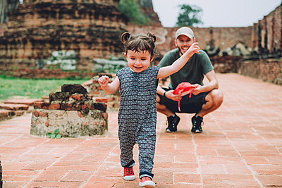 Thailand, Ayutthaya, Father observing his baby girl walking in the ancient ruins of a temple at Wat Mahathat - p300m2058724 von Gemma Ferrando