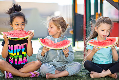 Three girls eating watermelons in kindergarten - p300m2104156 by zerocreatives