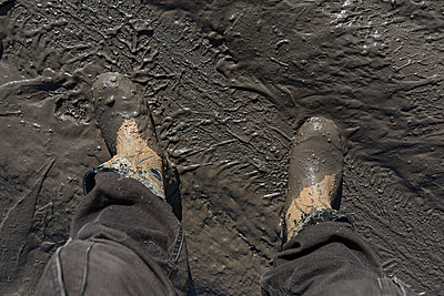 Construction worker's feet in mud of tyre track - p301m744231f by Vladimir Godnik