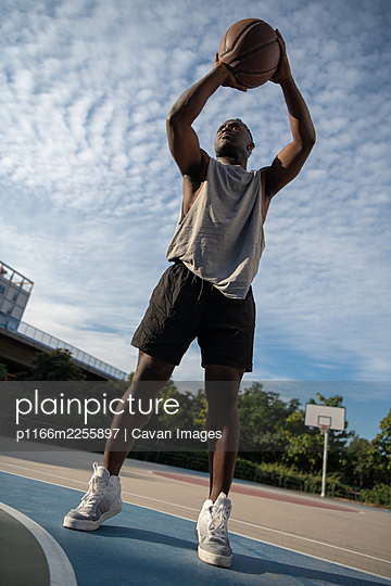 Muscular African American man scoring on basketball court - p1166m2255897 by Cavan Images