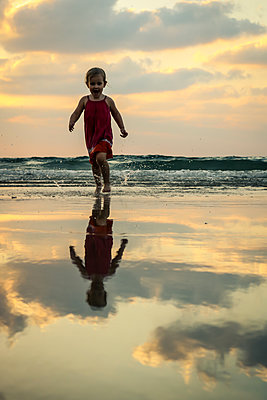 Child running on Beach at Sunset  - p1019m1467945 by Stephen Carroll