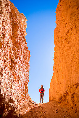 Low angle view of hiker standing by rock formations at Bryce Canyon National Park - p1166m1414731 by Cavan Images