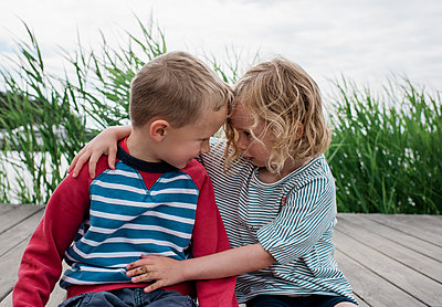 brother and sister looking at each other at  the beach on vacation - p1166m2129973 by Cavan Images