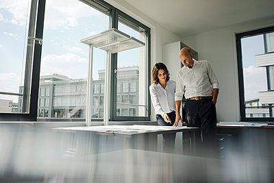 Two architects working in office, discussing blueprints - p300m2029752 von Kniel Synnatzschke
