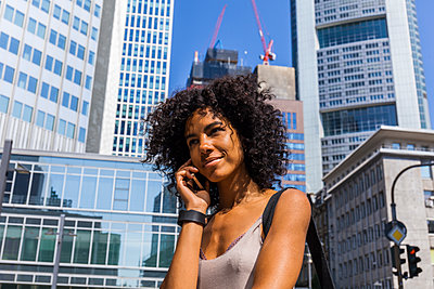 Germany, Frankfurt, portrait of smiling young woman on the phone - p300m2030364 by Tom Chance