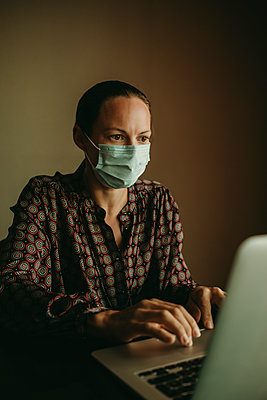 Concentrating female entrepreneur wearing protective face mask working on laptop in office - p300m2220733 by David Molina Grande