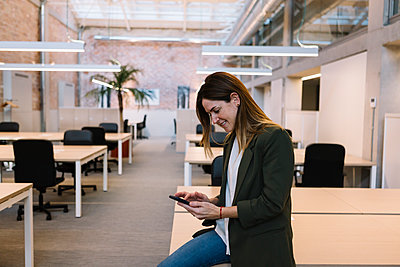 Businesswoman using smart phone while sitting on desk in office - p300m2276750 by Xavier Lorenzo