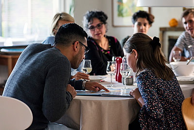 Man reading magazine to girl while sitting with friends and family at dinner party - p426m1212752 by Maskot