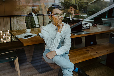 Businessman with hand on chin seen through glass at office - p426m2259365 by Maskot