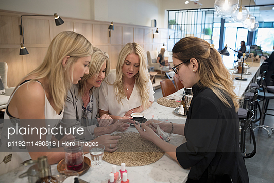 Female nail technician helping customers choose fingernail polish color in nail salon - p1192m1490819 by Hero Images