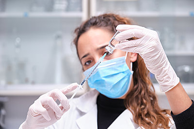 Young female scientist wearing face mask holding a coronavirus vaccine vial, syringe and needle. Covid-19 vaccine development.young, female, scientist, wearing, face, mask, holding, coronavir - p1166m2234610 by Cavan Images