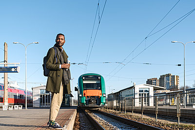 Portrait of stylish man with reusable cup waiting for the train - p300m2155355 by Hernandez and Sorokina