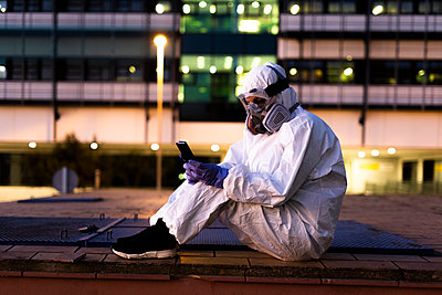 Female scientist wearing protective suit and mask using smartphone in front of a laboratory - p300m2170111 by Eloisa Ramos