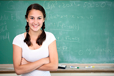 Portrait of teen girl in front of chalkboard - p3721879 by James Godman