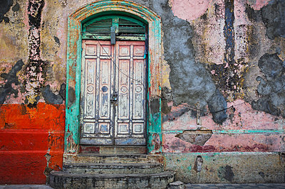 Worn and weathered facade of a building with peeling paint and double doors; Nicaragua - p442m1580590 by Henning Marstrand